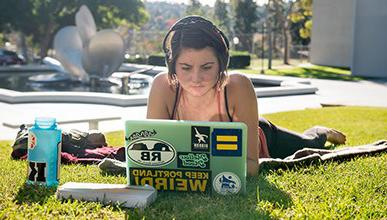 A student with headphones looks at her laptop while lying on the quad in front of Gilman Fountain