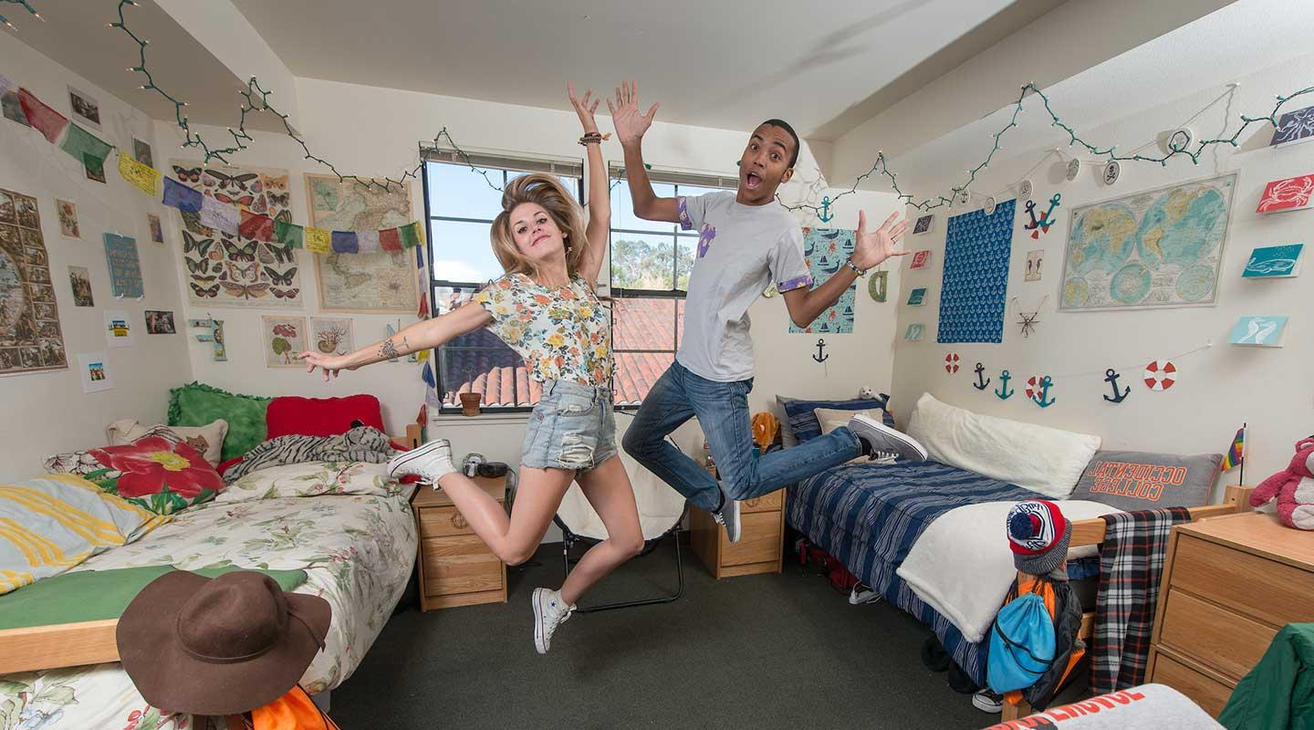Two students dancing playfully in a dorm room